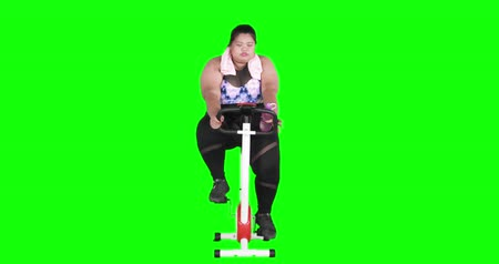 sede : Overweight woman drinking water with a bottle while riding exercise bike. Shot in 4k resolution with green screen background