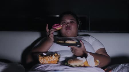 obżarstwo : Overweight woman eats donuts and others junk foods on the bed at night before sleep at home. Shot in 4k resolution
