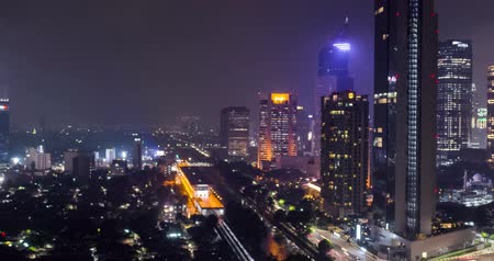 cemitério : JAKARTA, Indonesia - November 08, 2018: Beautiful hyperlapse footage of nighttime in Jakarta city with skyscrapers view and night lights. Shot in 4k resolution