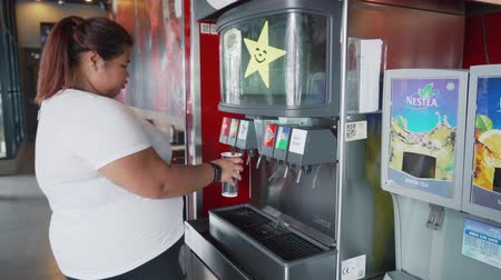 açucarado : JAKARTA, Indonesia - November 08, 2018: Overweight young Asian woman taking soft drinks refill on vending machine in the cafe. Shot in 4k resolution