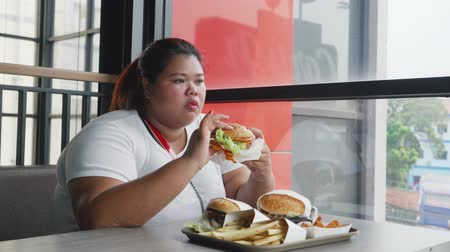 hranolky : Overweight young woman eating three big hamburgers in the cafe. Shot in 4k resolution