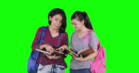 vysoká klíč : Two female high school students standing in the studio while reading books together. Shot in 4k resolution with green screen background