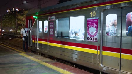 erkeklere özel : JAKARTA, Indonesia - November 13, 2018: Commuter train leaving the station with special train for women full of passengers Stok Video