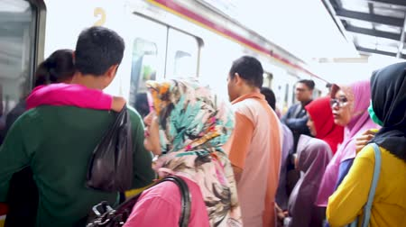 get out : JAKARTA, Indonesia - November 13, 2018: Crowded passengers get out and get in to the commuter train in the train station