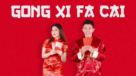 cai : Asian couple congratulate Happy Chinese New Year or Gong Xi Fa Cai while showing red envelopes and wearing traditional cheongsam. Shot in 4k resolution Stock Footage