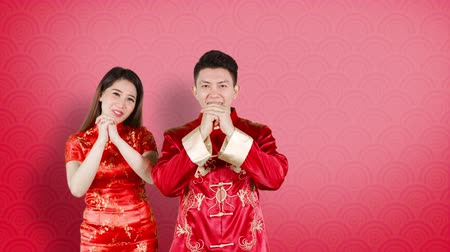cai : Asian couple greeting Happy Chinese New Year or Gong Xi Fa Cai while wearing red traditional cheongsam. Shot in 4k resolution
