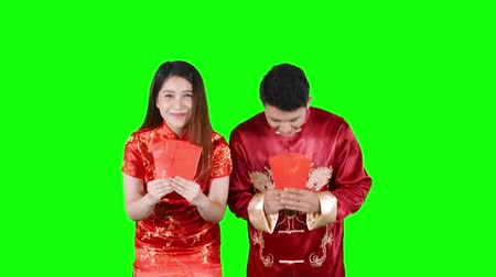 cai : Asian couple holding red envelopes and congratulate Chinese New Year while wearing traditional cheongsam. Shot in 4k resolution with green screen background