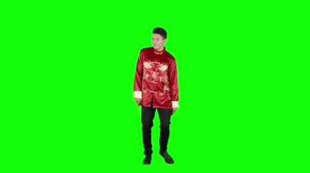 fulllength : Happy Asian man dancing in studio while holding red envelopes and wearing traditional cheongsam. Shot in 4k resolution with green screen background