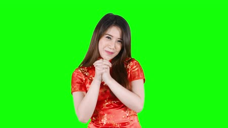gong : Happy Chinese New Year Concept. Asian woman in chinese dress traditional cheongsam with gesture of congratulation. Shot in 4k resolution with green screen background Stock Footage