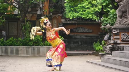 gelenek : Balinese dancer dancing Pendet Dance in a temple with traditional dress and a bowl of flower petals. Pendet is a traditional dance from Bali, Indonesia.