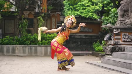 hindoe : Prachtige Balinese danseres dansen Pendet Dance in een tempel met een kom met bloembloemblaadjes en traditionele klederdracht. Pendet is een traditionele dans uit Bali, Indonesië.