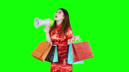 duyuru : Beautiful chinese woman speaking with a megaphone while holding shopping bags and wearing cheongsam dress in studio. Chinese New Year Concept. Shot in 4k resolution Stok Video