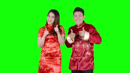 dedo humano : Cheerful Asian couple celebrating Chinese New Year while dancing and showing thumbs up with traditional cheongsam. Shot in 4k resolution