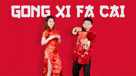 китайский новый год : Cheerful Asian couple holding red envelope on Chinese New Year or Gong Xi Fa Cai day celebration. Shot in 4k resolution with red background