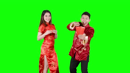 gong : Joyful Asian couple showing red envelopes on Chinese New Year or Gong Xi Fa Cai day celebration. Shot in 4k resolution with green screen background