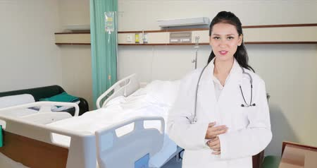 hastane : Young beautiful female doctor standing and speaking in the hospital room. Shot in 4k resolution Stok Video