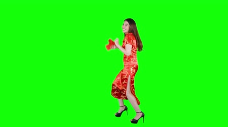fulllength : Happy Asian woman holding red envelopes and dancing in the studio while wearing traditional cheongsam on Chinese New Year day. Shot in 4k resolution with green screen background