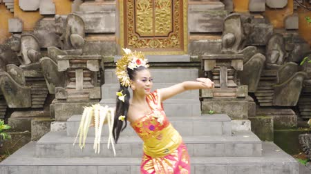 プルメリア : Pendet dancer dancing in a temple while holding a bowl of flower petals and wearing traditional dress. Pendet is a traditional dance from Bali, Indonesia. Shot in 4k resolution 動画素材