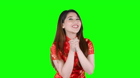 cai : Happy Chinese New Year Concept. Pretty Asian woman with congratulatory gesture while wearing traditional cheongsam. Shot in 4k resolution with green screen background Stock Footage