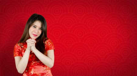 gong : Beautiful Asian woman congratulate Happy Chinese New Year while wearing traditional cheongsam. Shot in 4k resolution with red background