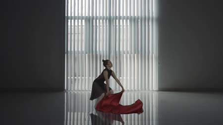 bale : Young woman dancing and jumping with red cloth near the window. Shot in the studio