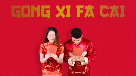 gong : Attractive Asian couple greeting Happy Chinese New Year or Gong Xi Fa Cai while holding red envelopes and wearing traditional cheongsam. Shot in 4k resolution