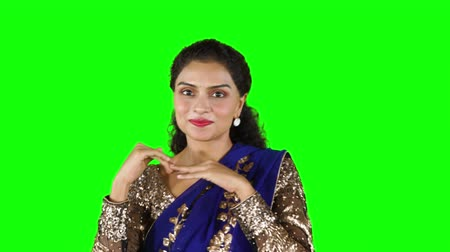 indian ethnicity : Attractive Indian woman dancing in the studio and smiling at the camera while wearing sari clothes. Shot in 4k resolution
