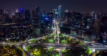 sudirman : JAKARTA, Indonesia - November 21, 2018: Beautiful hyperlapse of Semanggi highway interchange with light trails and office buildings view at night. Shot in 4k resolution