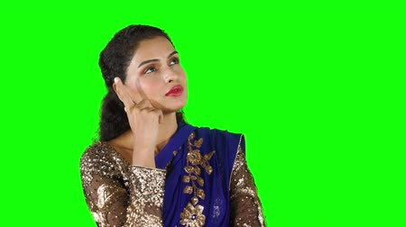 asian and indian ethnicities : Beautiful Indian woman wearing traditional sari clothes and thinking idea while looking upwards in studio. Shot in 4k resolution with green screen background Stock Footage
