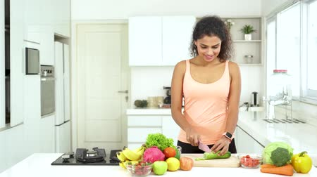 brócolis : Beautiful young Indian woman slicing vegetables and fruits to make salad in the kitchen at home. Shot in 4k resolution Stock Footage
