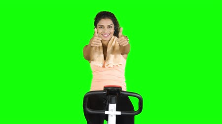 paquistão : Pretty young woman showing thumbs up while doing workout on exercise bike and smiling at camera in the studio. Shot in 4k resolution