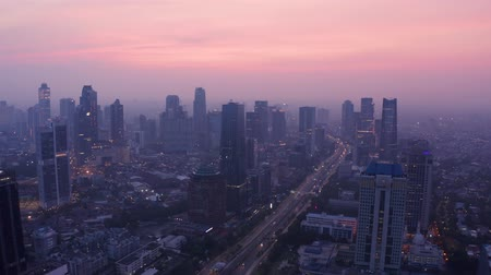 небоскреб : JAKARTA, Indonesia - November 26, 2018: Beautiful aerial scenery of Jakarta skyline at dawn with highway traffic and skyscrapers view. Shot in 4k resolution
