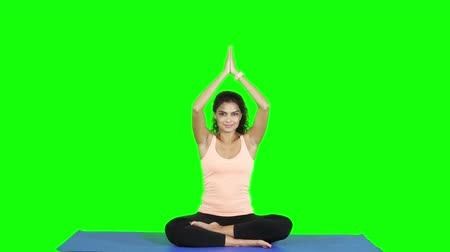 paquistão : Attractive young woman practicing yoga and meditation in the studio. Shot in 4k resolution with green screen background