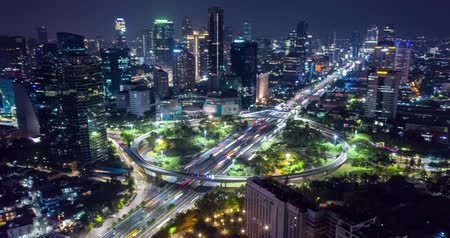 csomópont : JAKARTA, Indonesia - November 26, 2018: Beautiful hyperlapse of Semanggi bridge with light trails and modern office buildings view at night in Jakarta city. Shot in 4k resolution Stock mozgókép