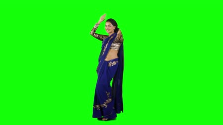 comprimento total : Full length of beautiful Indian woman wearing saree clothes and dancing in the studio. Shot in 4k resolution with green screen background