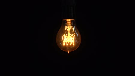 вольфрам : Power saving concept. Old light bulb glowing on dark background in the studio. Shot in 4k resolution