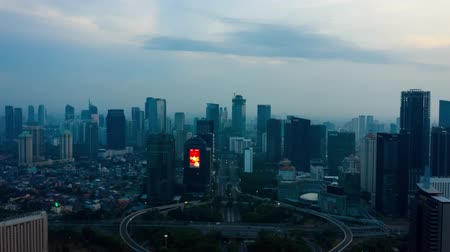 sudirman : JAKARTA, Indonesia - November 26, 2018: Beautiful aerial hyperlapse of highway traffic at Semanggi bridge with video advertising display on skyscraper. Shot in 4k resolution