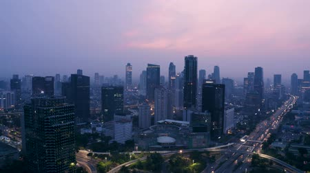központi : JAKARTA, Indonesia - November 26, 2018: Beautiful aerial view of skyscrapers and highway traffic near Semanggi bridge at dawn in Jakarta city. Shot in 4k resolution Stock mozgókép
