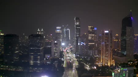backwards : JAKARTA, Indonesia - November 26, 2018: Beautiful aerial landscape of highway traffic and skyscrapers at night in Jakarta downtown. Shot in 4k resolution Stock Footage