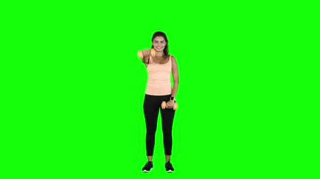 paquistão : Pretty young woman doing workout with dumbbells in the studio. Shot in 4k resolution with green screen background