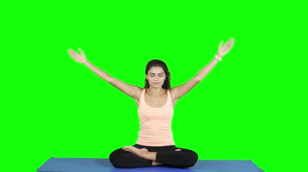 colchão : Beautiful young woman meditating and practicing yoga position while sitting on mattress. Shot in 4k resolution with green screen background Stock Footage