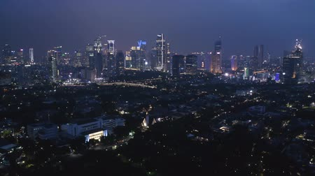 central business district : JAKARTA, Indonesia - December 14, 2018: Beautiful aerial Jakarta skyline at night with residential houses and skyscrapers view. Shot in 4k resolution Stock Footage