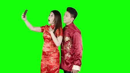 Çin yeni yıl : Happy Asian couple making video call with a mobile phone while wearing red cheongsam clothes in the studio. Shot in 4k resolution with green screen background