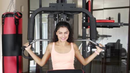 vzpírání : Beautiful Asian woman doing exercise on exercise machine while smiling at the camera in fitness center. Shot in 4k resolution Dostupné videozáznamy