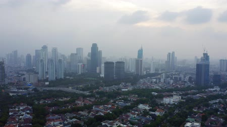central business district : JAKARTA, Indonesia - December 14, 2018: Beautiful aerial view of Jakarta downtown on misty morning with residential houses and skyscrapers view. Shot in 4k resolution