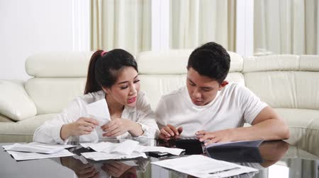 makbuz : Young couple counting their long bills paper with calculator in the living room at home. Shot in 4k resolution