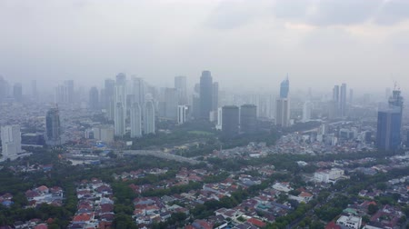 backwards : JAKARTA, Indonesia - December 14, 2018: Beautiful aerial view of residential houses and skyscrapers on misty morning in Jakarta city. Shot in 4k resolution Stock Footage