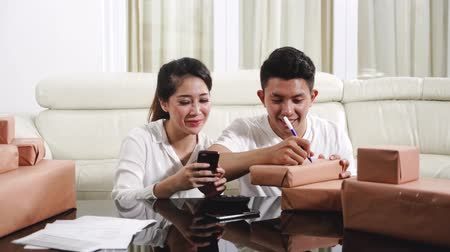 retailer : Online shop seller concept. Young couple preparing their product and write the address on table at home to send for their customer Stock Footage