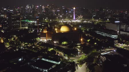történelmi : JAKARTA, Indonesia - December 12, 2018: Beautiful aerial landscape of Istiqlal Mosque with skyscrapers and National Monument background at night. Shot in 4k resolution
