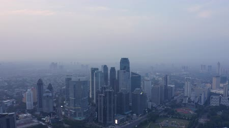 митрополит : JAKARTA, Indonesia - December 12, 2018: Beautiful aerial view of misty morning with silhouette of skyscrapers in Jakarta downtown. Shot in 4k resolution Стоковые видеозаписи